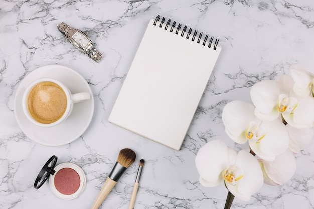Lege spiraalvormige blocnote; polshorloge; koffiekop; compact poeder; make-upborstel en witte orchideebloem op marmeren geweven achtergrond