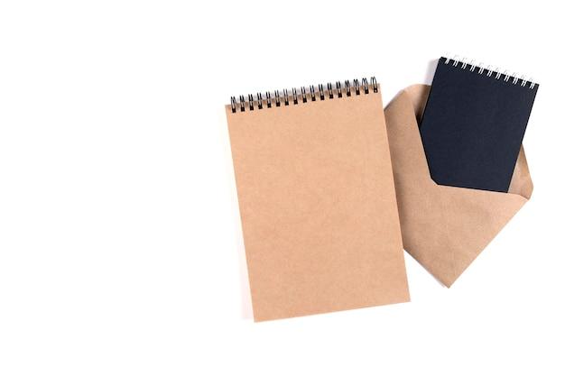 Lege spiraalvormige blocnotes en een gerecyclede envelop gestapeld op een witte achtergrond. onderwijs, kantoor, milieubescherming, nul afval.