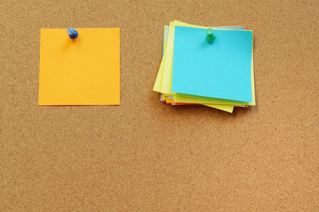 Lege stinkende notities pin op cork board. kurk bord met lege notities.