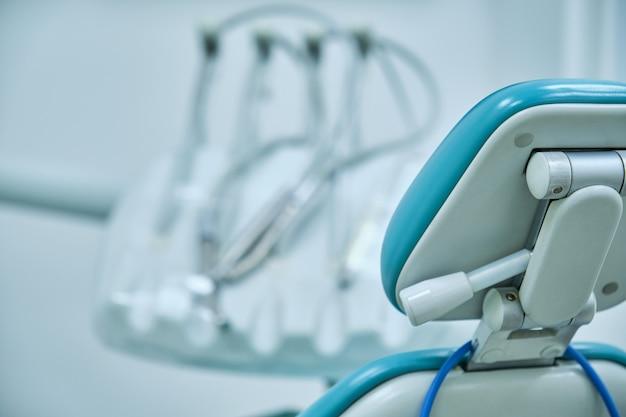 Lege stoel van een tandheelkundige kliniek met ongerichte achtergrondinstrumenten