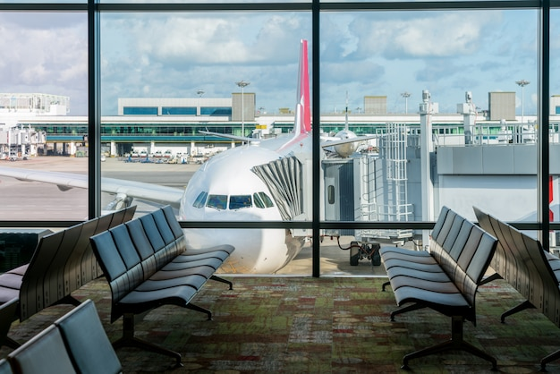 Lege stoelen in de vertrekhal op luchthaven met vliegtuigparkeren.