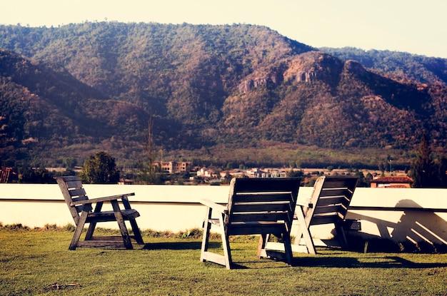 Lege stoelen op grasveld onder de natuur van de bergen