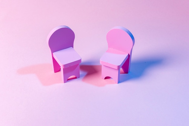 Lege stoelen tegen roze achtergrond