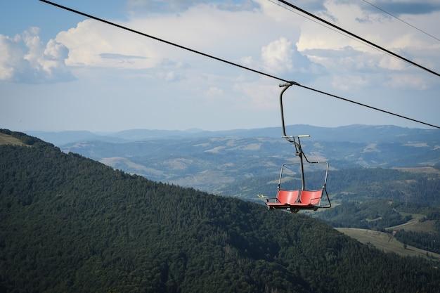 Lege stoeltjeslift op een achtergrond van prachtige herfst bergen.