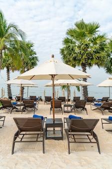 Lege strandstoel met palmboom op strand met zee