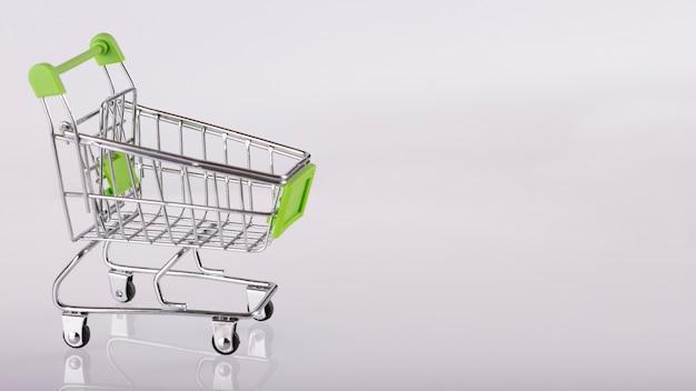 Lege supermarktkarretje op witte achtergrond, close-up