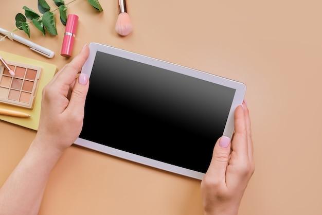 Lege tablet in de handen van de vrouw nexto schoonheidstoebehoren
