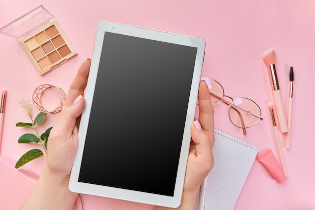 Lege tablet in handen van de vrouw, glazen, pennen, schoonheidsaccessoires, toetsenbord, kantoorbenodigdheden, groen blad op roze oppervlak