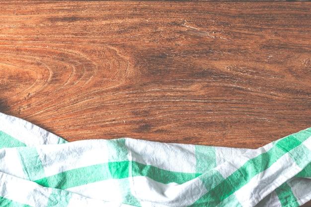 Lege tafel bedekt met tafellaken over bruin cement muur achtergrond,