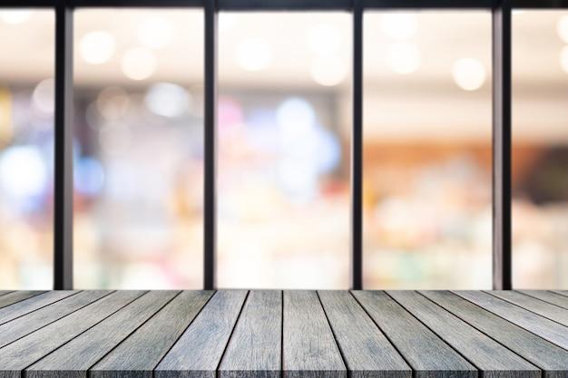 Lege tafel van de perspectief de houten raad bovenop bovenkant over de vage achtergrond van de koffiewinkel