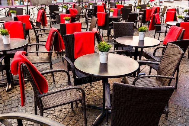 Lege tafels en rieten stoelen op straatstenen in een café in de oude stad