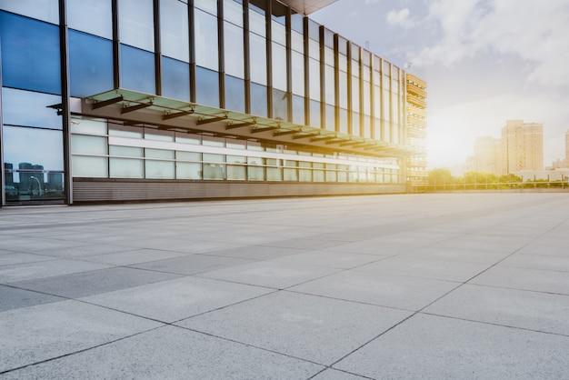 Lege tegelvloer met modern gebouw op de achtergrond
