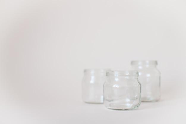 Lege transparante potten voor babyvoeding op grijs.