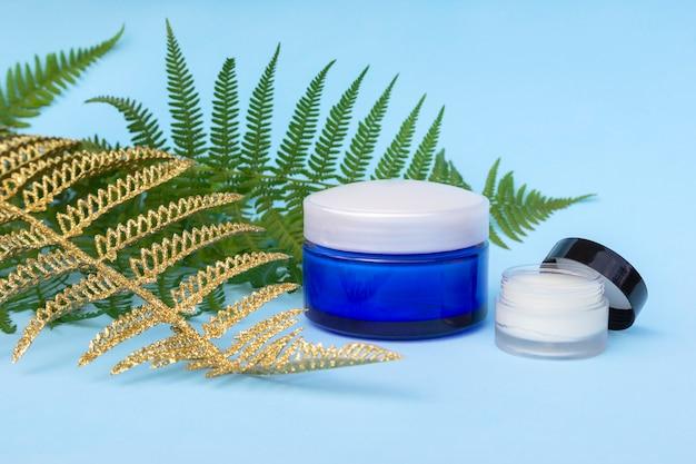 Lege twee potjes crème met natuurlijke, gouden varens palmbladeren.