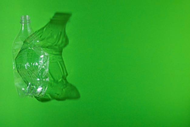 Lege verkreukelde gebruikte plastic fles op groene achtergrond