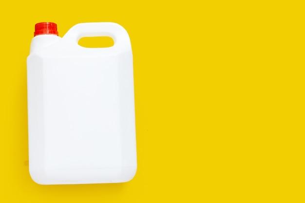 Lege verpakking witte plastic gallon op gele achtergrond.