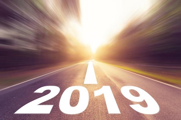 Lege vervaging asfaltweg en nieuwjaar 2019 concept. rijden op een lege weg naar doelen 2019.