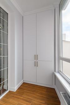 Lege verwarmde penthouse of lodge woonkamer met houten laminaatvloer en ramen op volledige hoogte en ingebouwde kast