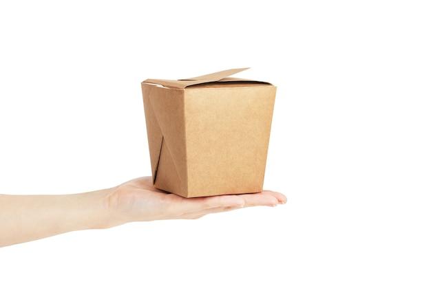 Lege vierkante kartonnen doos gemaakt van kraft-materiaal bij de hand op isoleren witte achtergrond. kopieer de ruimte, bespotten, zijaanzicht. fast food levering in de doos van de boodschappen. Premium Foto
