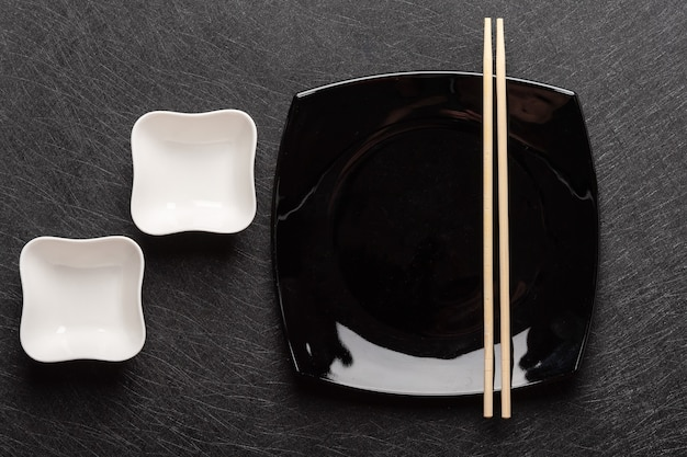 Lege vierkante zwarte plaat met eetstokjes en twee witte jusboten op een donkere japanse achtergrond