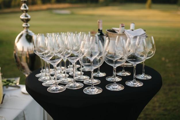 Lege vine glazen op tafel buiten op coupryside avondfeest