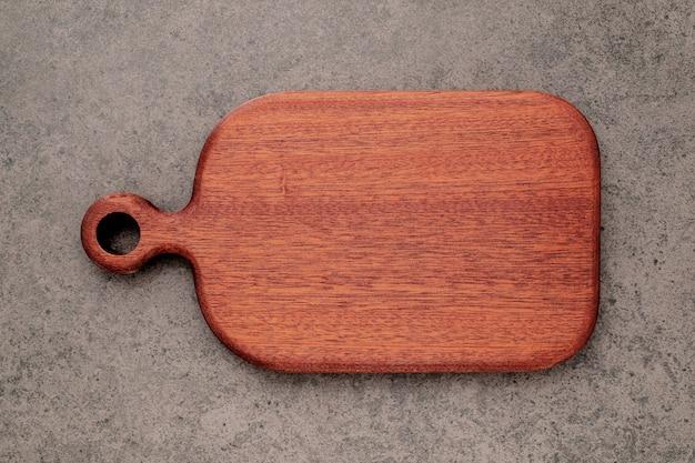 Lege vintage houten snijplank opgezet op donkere betonnen achtergrond met kopieerruimte.