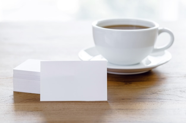 Lege visitekaartjes en kopje koffie op houten tafel.