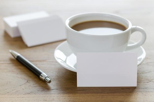 Lege visitekaartjes, pen en kopje koffie op houten tafel.