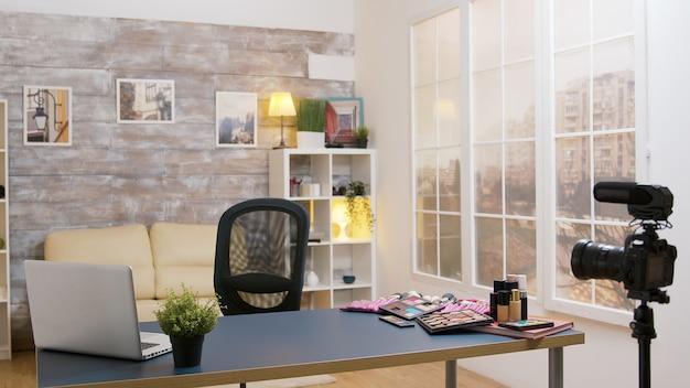 Lege vloggerruimte met schoonheidscosmetica op tafel en een videocamera vooraan klaar voor opname.