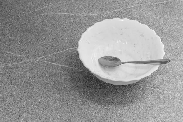 Lege vuile witte plaat met wat dessertkruimels en een lepel op grijze betonnen ondergrond, bovenaanzicht, zwart-wit, kopieer ruimte