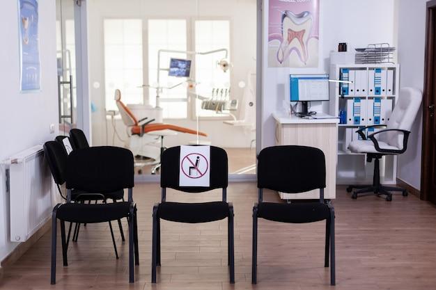 Lege wachtruimte, stomatologie-ontvangst met niemand erin met nieuw normaal met teken op stoel voor sociale afstand tijdens covid-19-epidemie