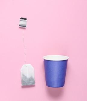 Lege wegwerp papieren beker voor thee, theezakje op roze pastel, bovenaanzicht