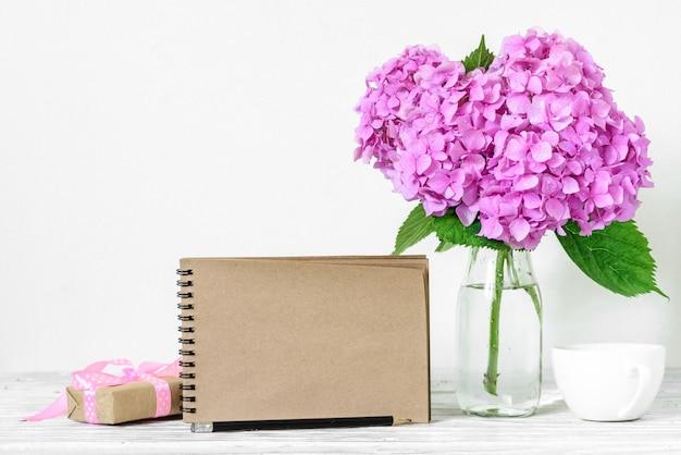 Lege wenskaart en blauwe hortensia bloemen, koffiekopje en geschenkdoos op witte houten tafel