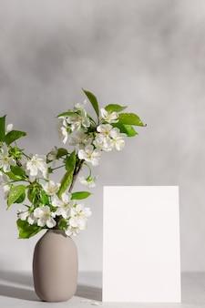 Lege wenskaart en boombloesems in vaas in zonlicht
