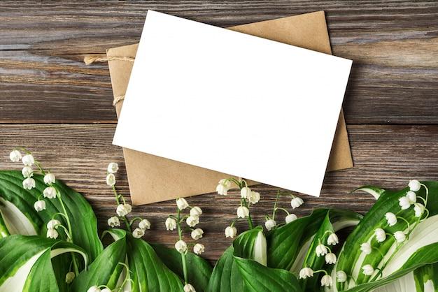 Lege wenskaart en envelop met lelietje-van-dalen bloemen op rustieke houten. plat lag