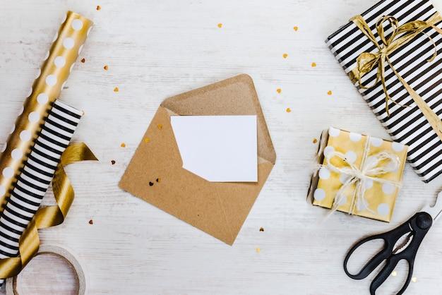 Lege wenskaart in een ambachtelijke envelop, geschenkdozen en inpakmaterialen op een witte houten achtergrond.