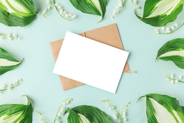Lege wenskaart in frame gemaakt van lente lelietje-van-dalen bloemen op pastelblauw oppervlak