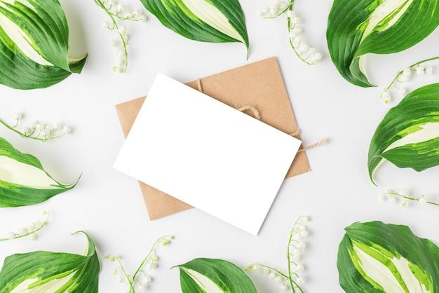 Lege wenskaart in frame gemaakt van lente lelietje-van-dalen bloemen op witte ondergrond