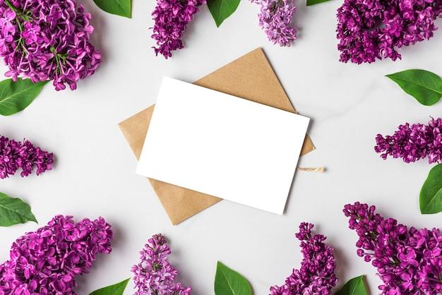 Lege wenskaart in frame gemaakt van lente lila bloeiende bloemen op witte ondergrond