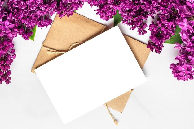 Lege wenskaart met lente lila bloeiende bloemen op witte ondergrond