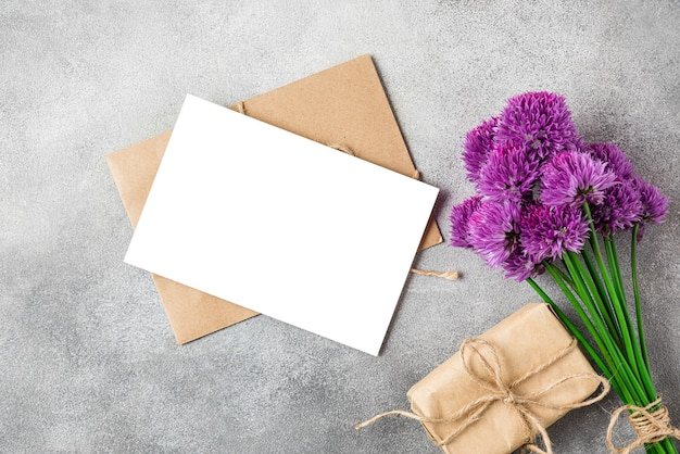 Lege wenskaart met paarse wilde bloemen boeket en geschenkdoos op betonnen ondergrond