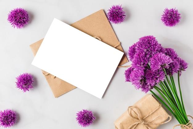 Lege wenskaart met paarse wilde bloemen boeket en geschenkdoos op witte ondergrond