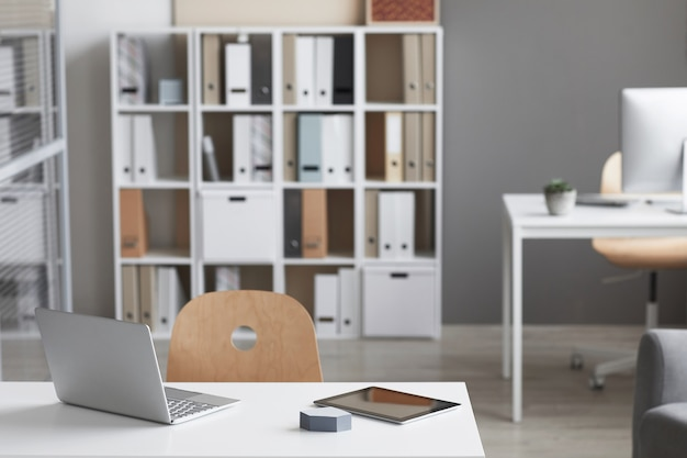 Lege werkplek met laptop en boekenkast op de achtergrond bij modern kantoor