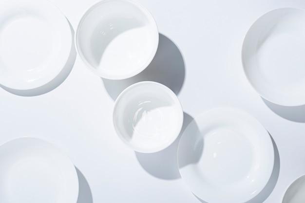 Lege witte borden, gerechten op een witte achtergrond. bovenaanzicht, plat gelegd.
