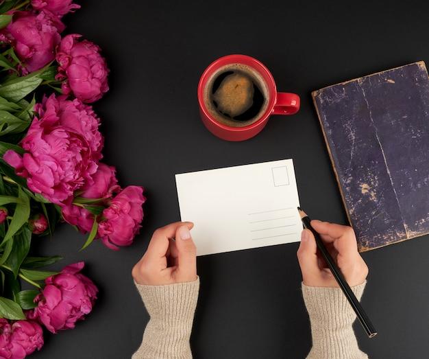 Lege witte briefkaart en twee vrouwelijke handen, op de tafel een boeket van rode pioenrozen en een keramische kopje koffie