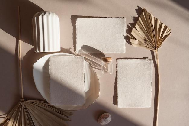 Lege witte bruiloft wenskaart met tag, gedroogde tropische palmbladeren, vaas plaat, op houten getextureerde tafel elegante moderne sjabloon. plat lag bovenaanzicht