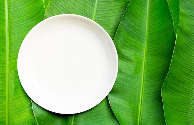 Lege witte ceramische plaat op de achtergrond van bananenbladeren. bovenaanzicht