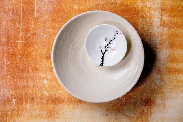 Lege witte ceramische platen met japanse chinese stijl het schilderen sakura bloeiende tak over oranje steenmuur. plat leggen, ruimte.