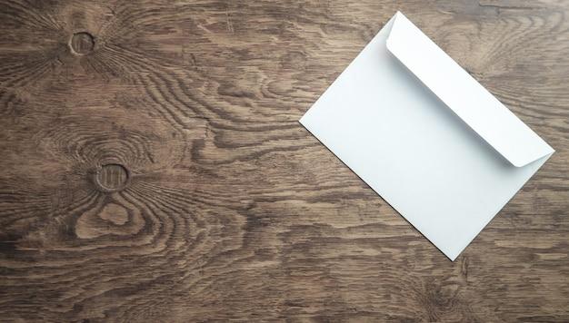 Lege witte envelop op houten achtergrond.