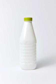 Lege witte fles voor zuivelproducten met groene omslag van kunststof, op een lichtgrijze achtergrond, kopie ruimte.
